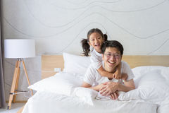 Happy asian family father and daughter smiling on bed Royalty Free Stock Images