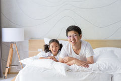 Happy asian family father and daughter smiling on bed Royalty Free Stock Photos