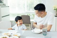 Happy Asian family of father and son playing and laughing while having dinner. Happy Asian family of father and son playing and laughing while having dinner Royalty Free Stock Photography