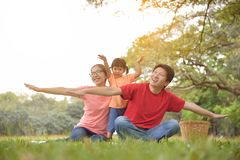 Happy Asian family having fun. Happy young Asian family with their daughter having fun in nature at park outdoor royalty free stock photography