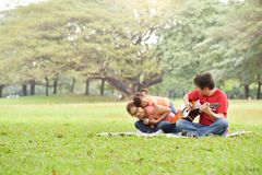 Happy Asian family having fun. Happy young Asian family with their daughter having fun in nature at park outdoor royalty free stock images