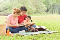 Happy Asian family having fun. Happy young Asian family with their daughter Reading a book. People having fun in nature at park outdoor stock photo