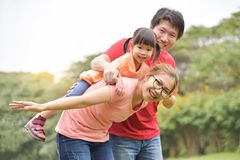 Happy Asian family having fun in nature. Happy Asian family having fun in nature at park outdoor. Young mother is carrying her daughter on her back. Copy space stock images