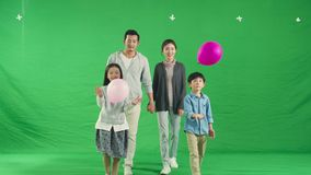Happy asian family having fun together. Happy asian family with two children having fun walking playing with balloons, shot against green background stock video