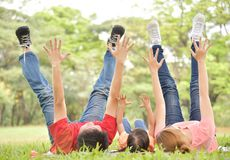 Happy Asian family having fun. Happy young Asian family with their daughter are lying and raised hands and legs up on green grass in nature at park outdoor royalty free stock photos