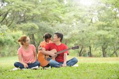 Happy Asian family having fun. Happy young Asian family with their daughter having fun in nature at park outdoor stock photography