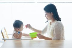 Mother feeding toddler. Royalty Free Stock Photos