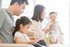 Happy Asian family lifestyle. Happy Asian family at home, father and daughter playing tablet pc, natural living lifestyle indoors Royalty Free Stock Photos