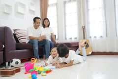 Happy asian family in living room at home. Togetherness relaxation concept stock photography