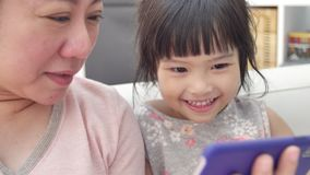 Happy asian family mother and daughter watching on phone and expand with smile face. Happy asian family mother and daughter are watching on phone and expand stock video footage