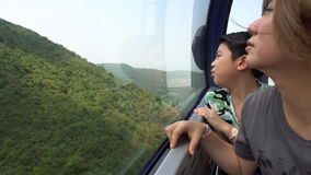 Happy asian family ,Mother and son in cable car ,looking nature hill stock footage