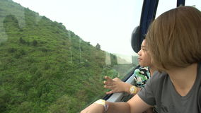 Happy asian family ,Mother and son in cable car ,looking nature hill stock video footage
