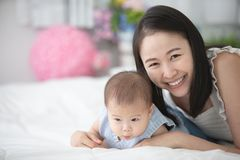 Happy asian family mother with son playing on bed with smile fac. E royalty free stock photos