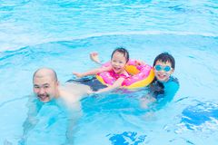 Happy family playing in swimming pool. Happy Asian family playing together in swimming pool Royalty Free Stock Image