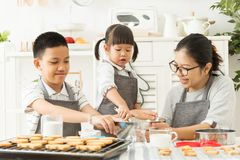 Happy Asian family preparing the dough. Happy Asian family preparing the dough bake for cookies and cakes in the kitchen Royalty Free Stock Photos