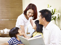 Happy asian family reading a book at home. Happy asian family with two children sitting on sofa reading a book together Royalty Free Stock Photography