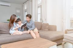 Happy asian family reading storybook at home royalty free stock images