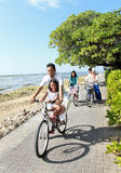 Happy asian family riding bikes in the beautiful morning at the Royalty Free Stock Image
