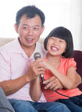 Happy Asian family singing karaoke royalty free stock photo