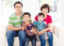 Happy asian  family sitting on a white leather sofa Royalty Free Stock Image