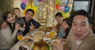 Happy Asian family taking selfie photo at a Christmas Party. Happy Asian family taking selfie photo at a Party. Happy friends enjoying christmas dinner together stock video footage