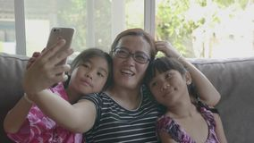 Asian Family Taking Selfie With Smartphone At Living Room. Happy Asian Family Taking Selfie With Smartphone At Living Room stock footage