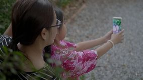 Asian Family Taking Selfie With Smartphone On A Outdoor Swing. Happy Asian Family Taking Selfie With Smartphone On A Outdoor Swing stock video
