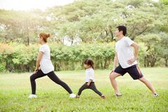 Happy Asian family workout at the park. Happy Asian family with their daughter in white shirt workout at the park. People are warming up and stretching their stock photo
