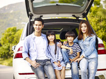 Happy asian family traveling by car. Happy asian family with two children posing with the car in which they are traveling Royalty Free Stock Image