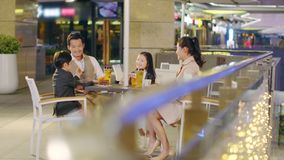 Happy asian family with two children having fun in coffee shop. Happy asian family with two children chatting relaxing having fun at a coffee place stock footage