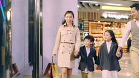 Asian family with two children shopping in mall
