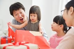 Happy Asian family unwrapping a gift box. Happy Asian little girl with her family unwrapping a red gift box for Birthday, Christmas and New year in a white room Royalty Free Stock Photo