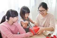 Happy Asian family unwrapping a gift box. Happy Asian family unwrapping a red gift box for Birthday, Christmas and New year in a white room at the house Stock Photo
