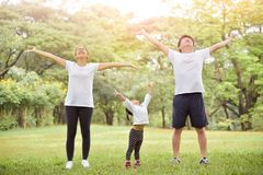 Happy Asian family workout at the park. Happy Asian family with their daughter in white shirt workout at the park. People are warming up and stretching their stock image