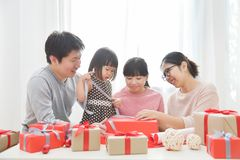 Happy Asian family wrapping a gift box. stock photography