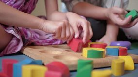 Young mother and her daughters are playing wooden toy block together at home.