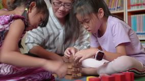 Young mother and her daughters try to build wooden block tower.