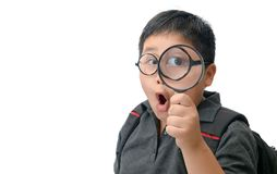 Happy asian fat boy holding magnifying glass. Happy asian school boy holding and looking through magnifying glass showing a big eye, isolated over white stock images