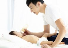 Happy father feeding baby from bottle stock photography