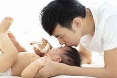 Happy father feeding baby from bottle royalty free stock photo