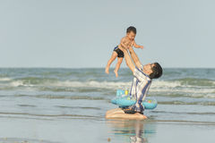Happy Asian father and son Having Fun on at tropical beach vacat. Happy Asian father and son Having Fun on beach vacation outdoors, shallow dof, vintage tone Stock Photo