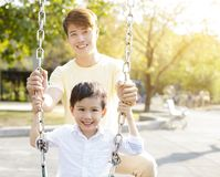 Happy father and son playing swing. Happy asian father and son playing swing Stock Images