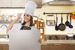 Happy asian female chef with ok gesture holding white board Stock Photography