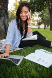 Happy asian female student sitting on grass with laptop and talk Stock Photo