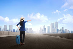Happy asian female traveler with hat and suitcase Stock Images