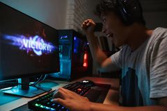Happy asian gamer boy winning while playing video games on compu. Ter in dark room wearing headphones and using backlit colorful keyboard royalty free stock photography