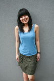 Happy Asian girl. Smiling leaning against a wall Stock Photography