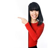 Happy asian girl. Pointing at a blank board Stock Image