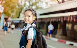 Happy asian girl arriving school from home with a backpack.  stock photos