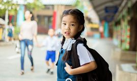 Happy asian girl arriving school from home with a backpack.  Royalty Free Stock Photo